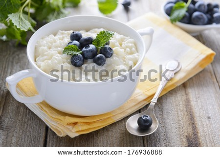 Rice pudding with bilberry in white bowl - stock photo