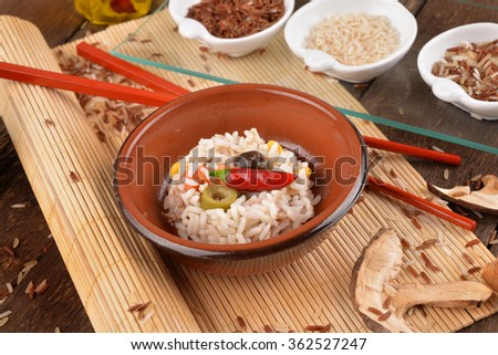Rice salad with vegetables on a mat makisu with oil and vinegar cruets