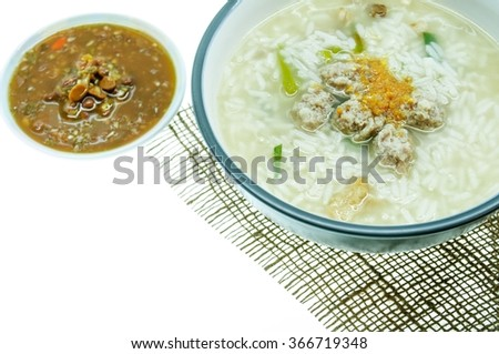 Rice soup with fried garlic and minced pork. On burlap background. With sauce made from  salted soybean mix with chili  on white background. Shallow depth of field. - stock photo