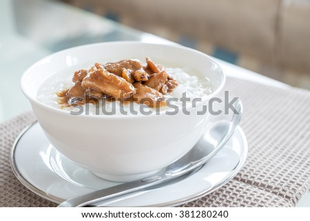 Rice soup with fried pork with garlic and pepper in white bowl