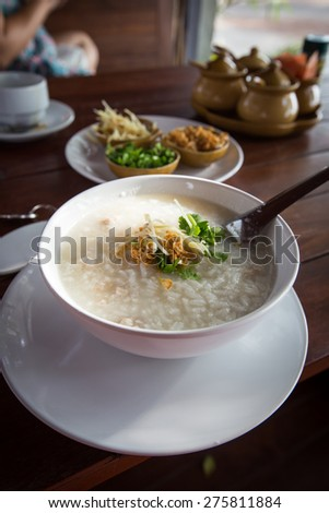 Rice soup with minced pork in the morning at the sea. - stock photo