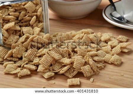 Rice squares breakfast cereal spilling out of a canister - stock photo