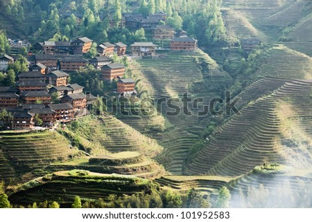 rice terraces and ethnic minority village at dusk in guangxi province,China