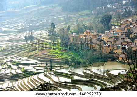 Rice terraces and village on hillside, Yuan Yang , China - stock photo