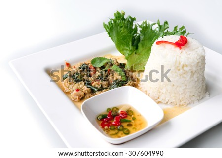 Rice topped with stir-fried pork and basil isolated on white background - stock photo
