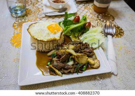 Rice topped with stir-fried pork and basil thai food with spoon - stock photo