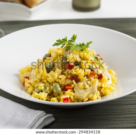 Rice with artichoke, beans and saffron. - stock photo
