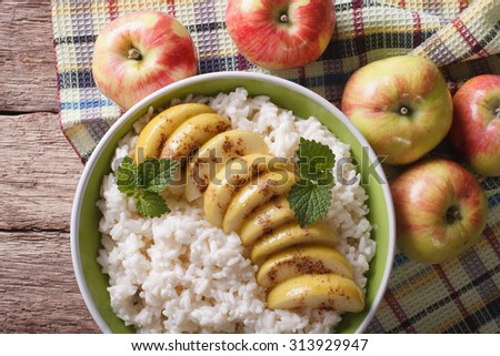 Rice with caramelized apples in a bowl and fresh apples on a table close up. horizontal view from above
