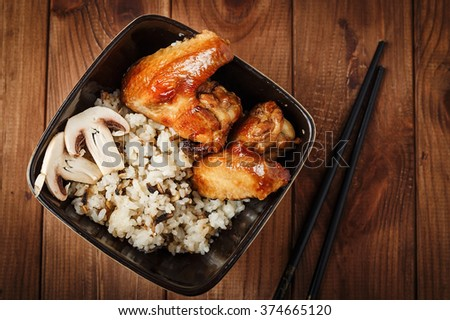 Rice with fried mushrooms and baked chicken wings on dark wooden background. Chinese cuisine. Selective focus - stock photo