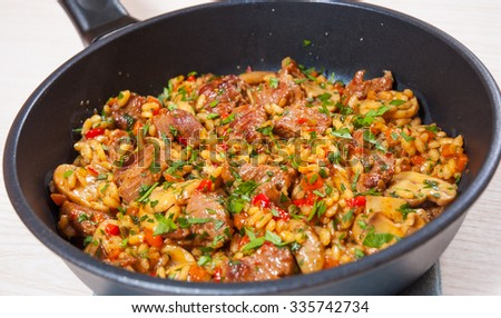 Rice with meat, vegetables and mushrooms in a frying pan