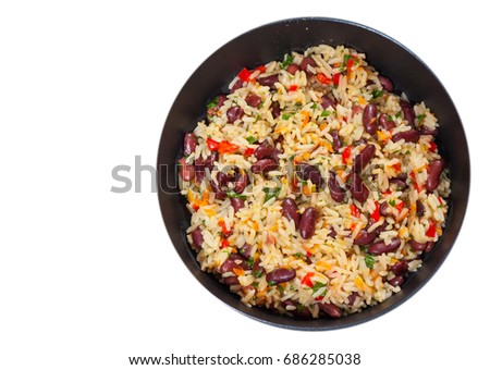 rice with red beans and vegetables in a frying pan. top view. isolated on white