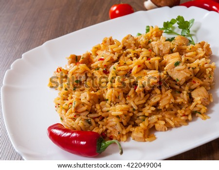 Rice with Vegetables and Meat in a plate on wooden table - stock photo
