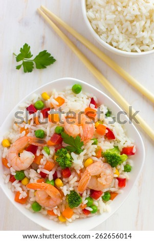 Rice with vegetables and shrimps on white background, top view - stock photo