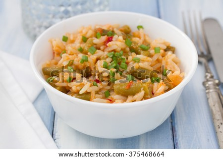 rice with vegetables in white bowl and glass of water