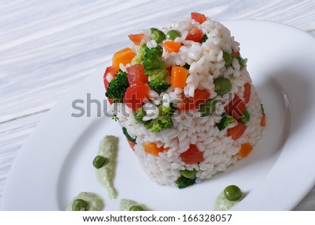 Rice with vegetables on a white plate with sauce