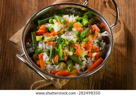Rice with vegetables on  wooden table. Selective focus. - stock photo