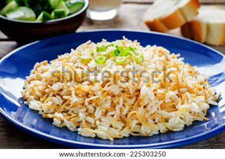 Rice with vermicelli on a dark wood background. Traditional Arabic dish. tinting. selective focus on green onions - stock photo