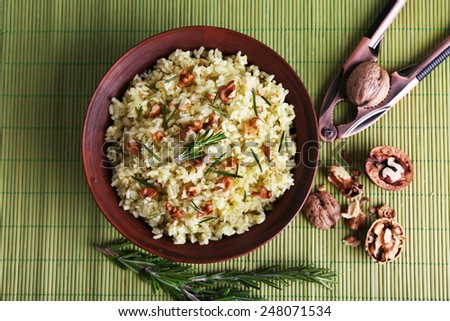 Rice with walnuts and rosemary in plate on bamboo mat background - stock photo
