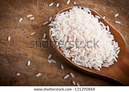 Rice with wooden spoon on wooden table. - stock photo