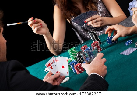Rich and elegant people gambling by a poker table