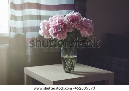 Rich bouquet of pink peony roses flowers in vase on table with sunlight background. Summer time concept. Still life, rustic style. Fresh floral, home decor. Place for text, copy space