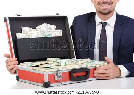 Rich buinessman. Happy young businessman in formalwear sitting at the table and holding a suitcase full of money while isolated on white - stock photo