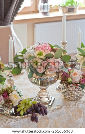 Rich bunch of anemones, tea roses, tulips, in vase on bride and groom table