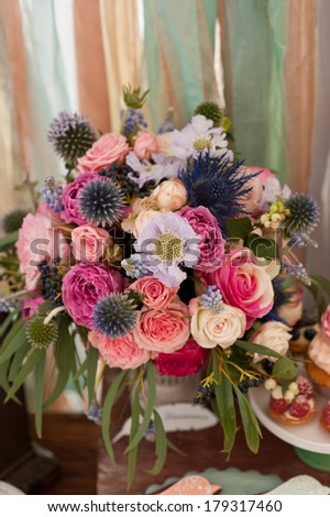 Rich bunch of flowers: peonies, tea roses, tulips, hydrangea in vase on bride and groom table