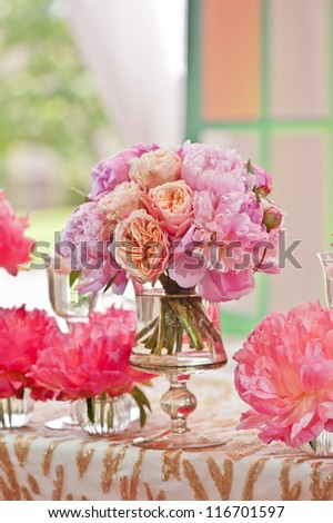 Rich bunch of peonies and tea roses in vase on bride and groom table