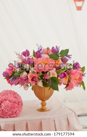 Rich bunch of peonies, tea roses, tulips, in vase on bride and groom table