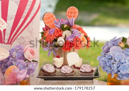Rich bunch of peonies, tulips, roses in vase on sweet table.  Cupcakes and  berries desserts.