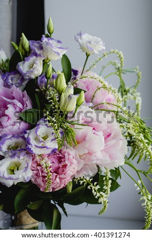 Rich bunch of pink peonies peony and lilac eustoma roses flowers in glass vase on white background. Rustic style, still life. Fresh spring bouquet, pastel colors. - stock photo