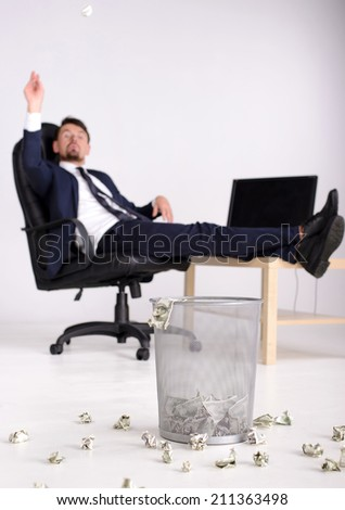 Rich businessman having fun in his office. Just outside the money in the trash. White background. - stock photo