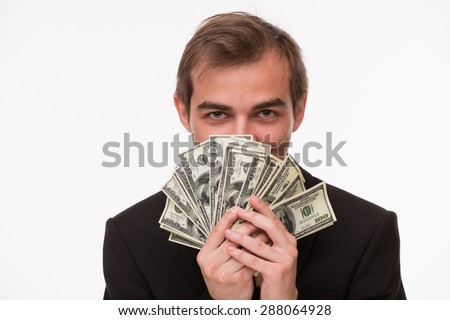 Rich businessman screening himself behind dollars. Man with rude character smiling on white background.