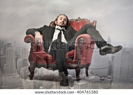 Rich businessman sitting in red chair - stock photo