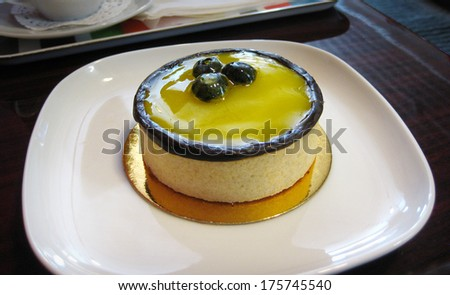 Rich colorful lemon tart rimmed with chocolate and topped with blueberries - stock photo
