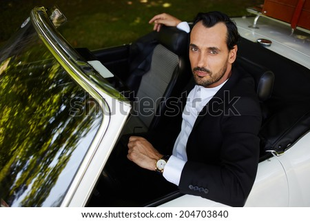 Rich confident businessman with gold wrist watch in the hand sitting in the cabriolet classic car and looking at camera, lifestyle and successful business concept