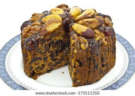 Rich fruit cake decorated with Brazil nuts. - stock photo