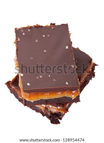 Rich, gooey good salted chocolate caramel brownies.  Shot on white background. - stock photo