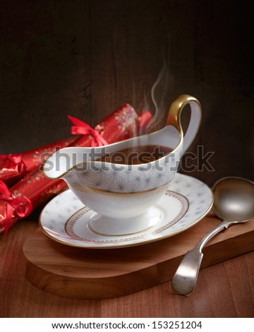 Rich gravy served in gravy boat with ladle and Christmas crackers - stock photo