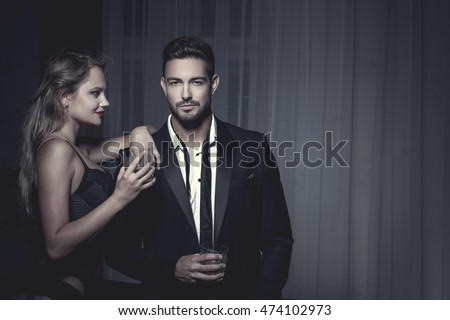 Rich macho young man drink whiskey with blonde lover at night