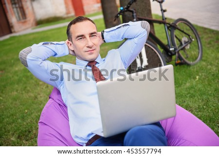 Rich man having rest with computer outdoors - stock photo