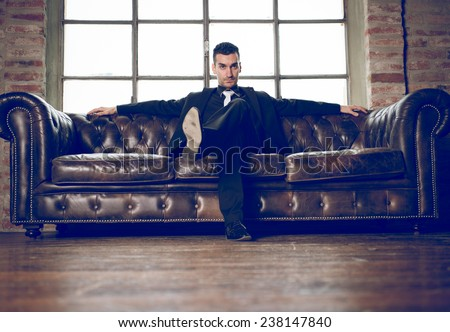 rich man sitting on a couch in a luxury apartment.  - stock photo