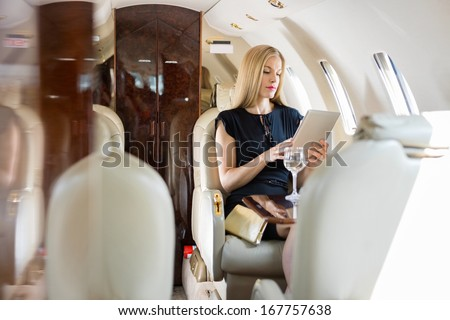 Rich mid adult woman using tablet computer in private jet - stock photo