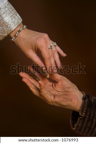 Rich person giving gold coin to beggar - stock photo