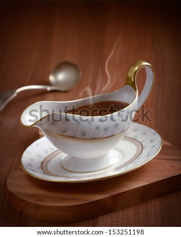 Rich steaming gravy with ladle - stock photo