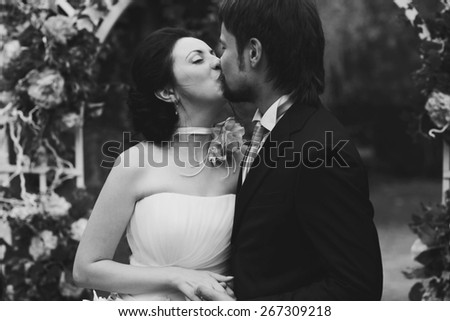 rich stylish happy bride and groom kissing near a white wedding arch decorated with flowers peonies Rome Italy black and white
