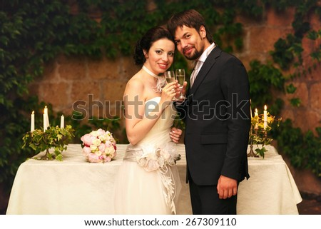 rich stylish happy bride and groom smiling  holding goblets with champagne  near a white wedding table decorated with flowers peonies and candles Rome Italy - stock photo