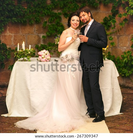 rich stylish happy bride and groom smiling  holding goblets with champagne  near a white wedding table decorated with flowers peonies and candles Rome Italy