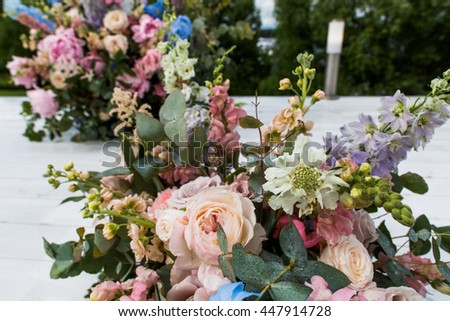 Rich summer bouquets stand on the white floor - stock photo